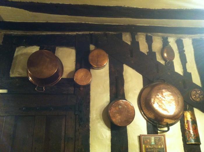 Panelas de cobre dependuradas na parede fazem parte de decoração da casa