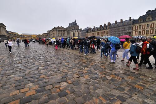 Sob chuva, turistas esperam na fila para entrar em Versailles.