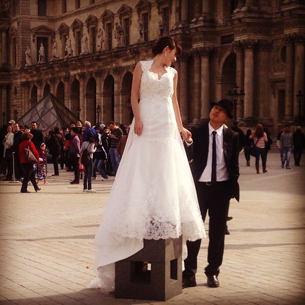Casal de noivos posam para fotos em frente à pirâmide do Louvre