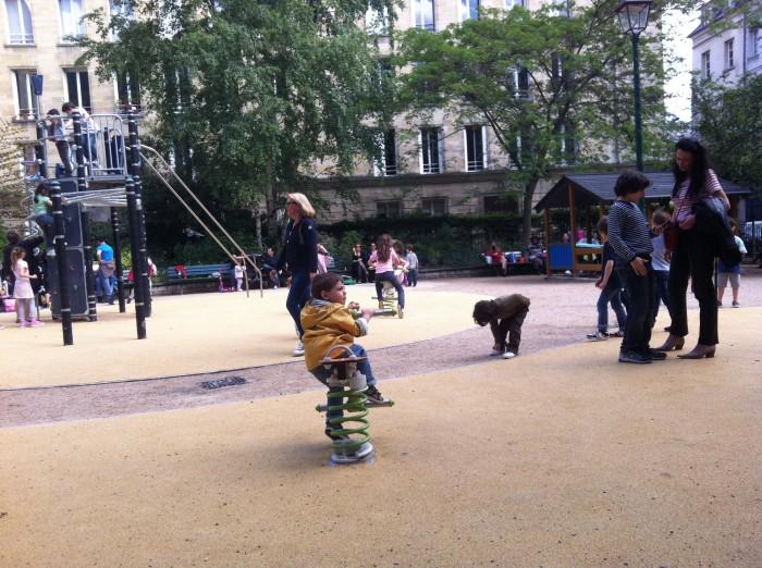 Pais e filhos, em parquinho no Marais