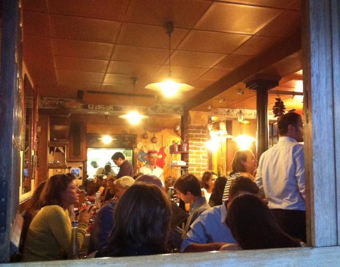 Pequeno salão do restaurante: mesas coladas e decoração rústica