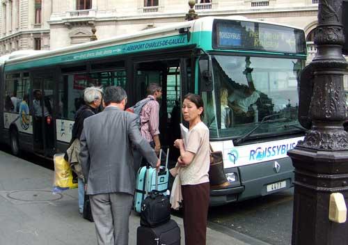 Turistas asiáticos na parada do ônibus Paris/CDG