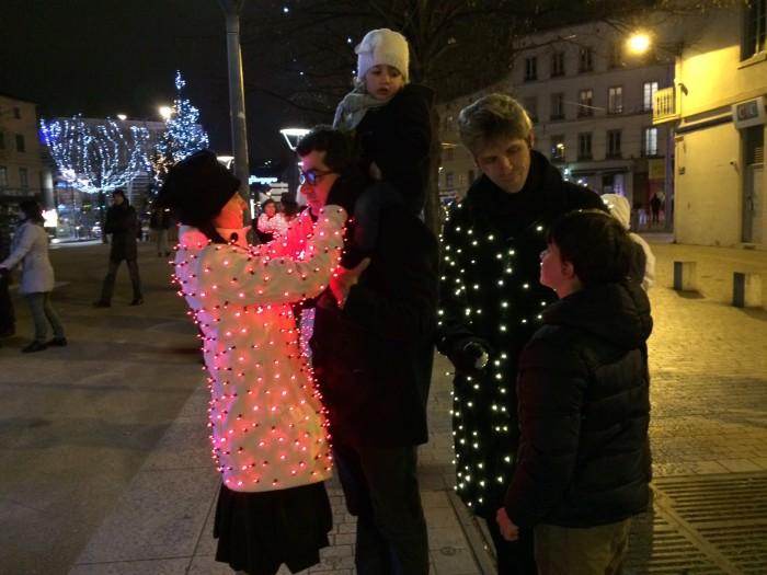 Seres com roupas iluminadas interagem com as pessoas nas ruas