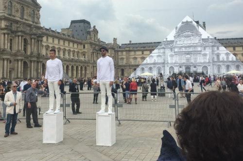 O artista JR posando em frente a sua obra na pirâmide do Louvre