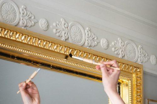 Finalização da douração da moldura de um espelho.