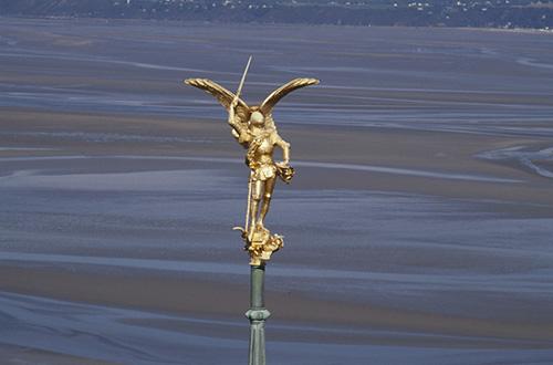 O arcanjo e no fundo a baia na maré baixa