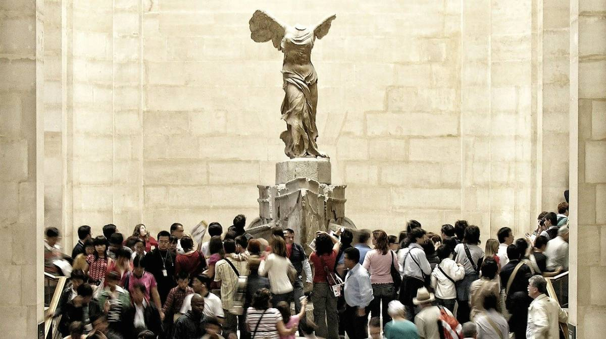 Museu do Louvre: a Vitória de Samotrácia e a multidão.